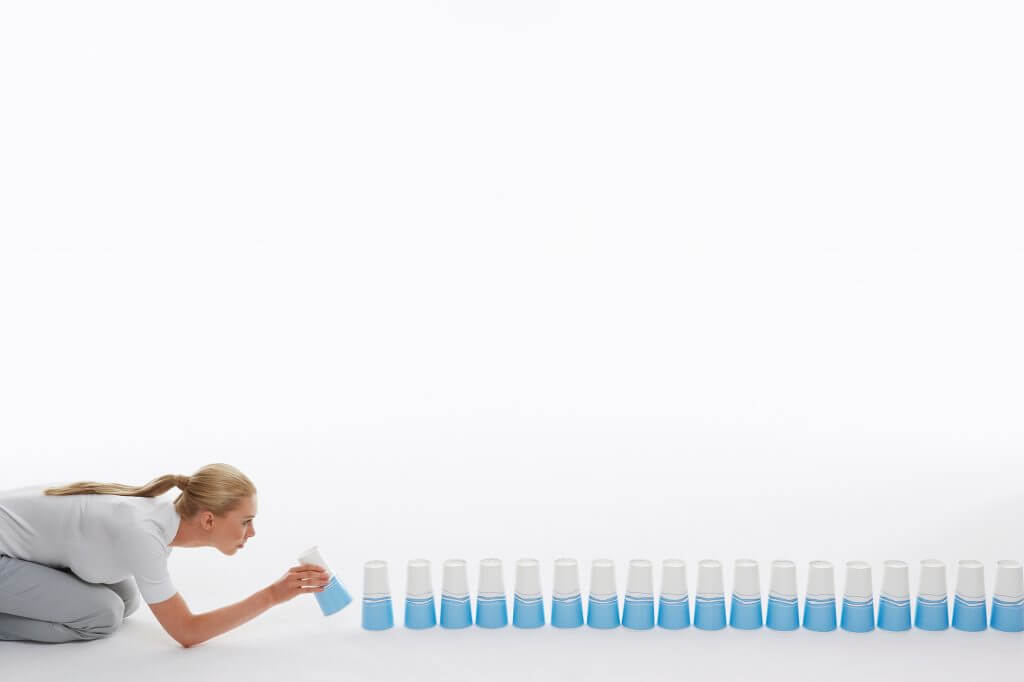 woman checking the alignment of a row of cups like one should check for business strategy and brand strategy alignment